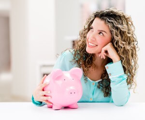 Thoughtful woman with a piggybank looking very happy